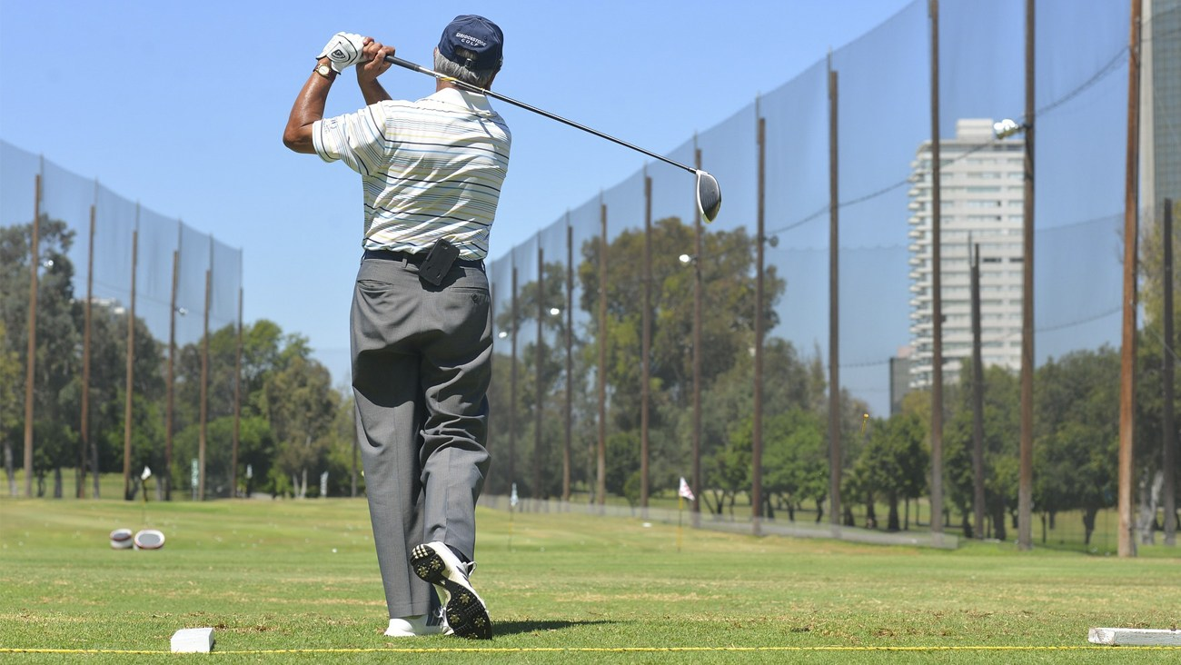 A senior golfer swinging a club.